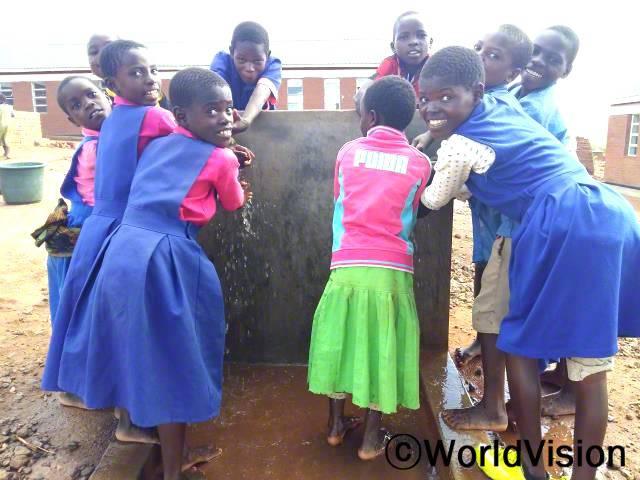 이제 학교에서도 깨끗한 물을 마실 수 있어요. 마실 물을 찾으러 시간을 쏟지 않아도 돼요. 공부할 수 있는 시간이 더 늘어서 기뻐요! -린다(12세, 앞줄 왼쪽에 있는 아동)년 사진