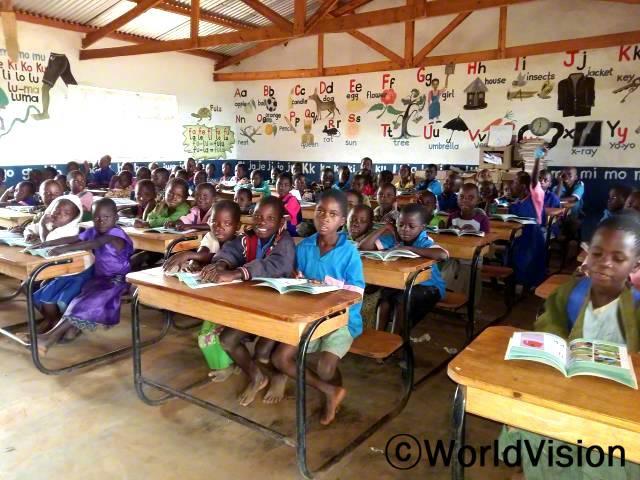 이제 우리 교실에 좋은 수업자료들이 생겨서 읽기와 수학 수업이 더 나아졌어요. 그리고 선생님과 학생들 모두 읽고 쓰는 것을 서로 잘 도와줘요. -모세(9세, 가운데 회색 자켓을 입은 아동)년 사진