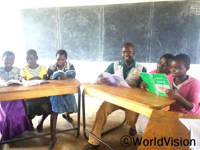 말라위 음페레레 지역개발사업장 팀장 해롤드 문탈리 씨와 지역사회 아동들이 함께 있는 모습입니다.년 사진