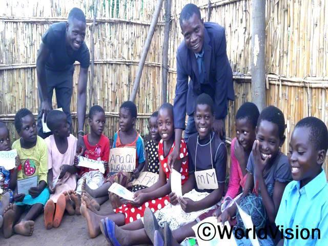 """""""월드비전이 30명의 독서 캠프 자원봉사자들을 추가로 훈련시켜 더 많은 아이들이 읽고 쓰는 법을 배울 수 있게 되었습니다."""" –블레싱(왼쪽에 서 있는 남성)년 사진"""