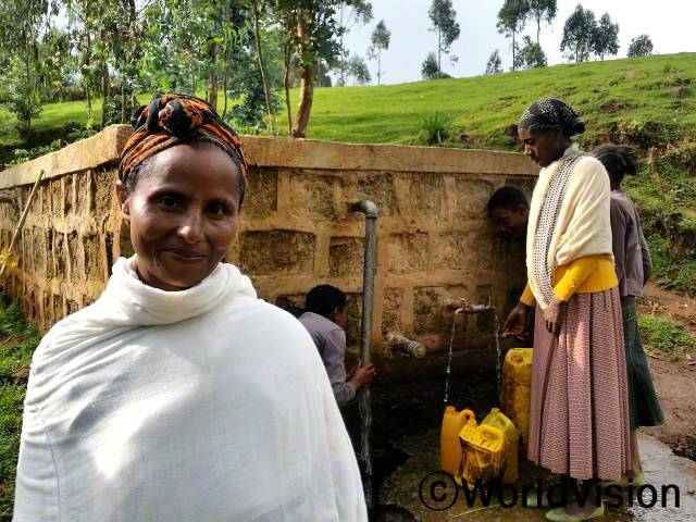 이제 저희는 안전하고 깨끗한 물을 마실 수 있게 되었어요. 샘에 물이 부족하거나 할 때에도 이전과 달리 물탱크에 물을 저장할 수 있어요. 저희 지역사회를 위해 이렇게 샘을 개발해 줘서 저희 모두 정말 감사해요.  -다섯 아이의 엄마 토비아(46세)년 사진