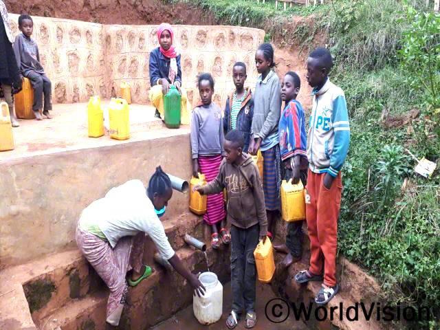 """""""전에는 물을 기르기 위해 먼 곳까지 가야 해서 공부할 시간이 없었어요. 하지만 후원자님 덕분에 마을에 식수시설이 생겨서 깨끗한 물을 마음껏 마실 수 있고 남는 시간에 공부도 할 수 있게 되었어요."""" –미소(13세)년 사진"""