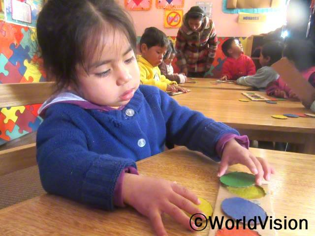 저는 작은 동그라미 모양에 잘 맞출 수 있어요. 저는 매일 다양한 모양과 색깔에 대해 배워요. 저는 모든 것을 제자리에 넣을 수 있어요. -메일리(3세, 파란색 스웨터를 입은 아동)년 사진
