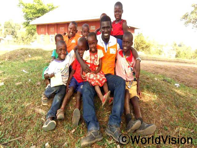 우간다 카삼브야 지역개발사업장 팀장인 데이비드 쎈임바와 함께 있는 아동들입니다.년 사진