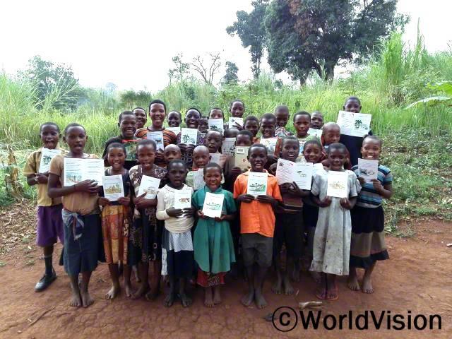 친구들과 함께 책을 읽어요. - 패트릭(9세, 왼쪽에서 첫 번째, 보라색 바지를 입은 아동) 월드비전은 마을에 교육 자료를 지원하며 아동들의 공부를 돕습니다.년 사진