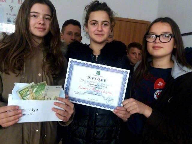 오로라(13세, 갈색 코트를 입은 아동)는 문학 경연 대회에서 받은 상금을 도움이 필요한 가정들에게 기부했습니다.년 사진