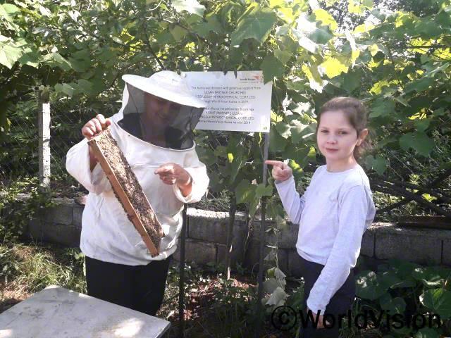 """""""할머니가 양봉하러 가실 때, 따라가는 건 정말 재미있어요. 어떻게 벌들이 움직이는지 볼 수 있거든요. 처음에는 1개였는데, 지금은 5개가 넘는 벌집통이 생겼어요.할머니께서는 꿀을 팔아서 우리에게 필요한 것도 사주시고요, 또 언니와 저는 매일 아침마다 꿀을 먹어요.""""  - 파비아나(10세)년 사진"""
