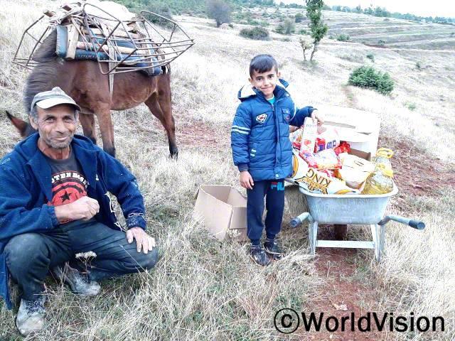 """""""오늘은 참 감사한 날입니다. 저는 외국에서 일하고 있는 이 아이의 부모를 대신해서 아이들을 돌보고있는데, 아이와 함께 먹을 수 있는 식료품을 지원받아 정말 안심입니다."""" -카드리(65세, 할아버지)년 사진"""