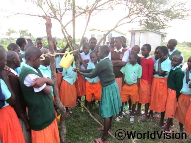 학교 위생을 개선하고자 손을 씻을 수 있는 간이 수도꼭지를 만들고 뿌듯해하는 파지아니 초등학교 학생들년 사진