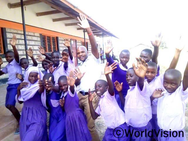 케냐 밤바 지역개발사업장 팀장 알렉슨 음와시 씨와 지역사회 아동들의 모습입니다.년 사진