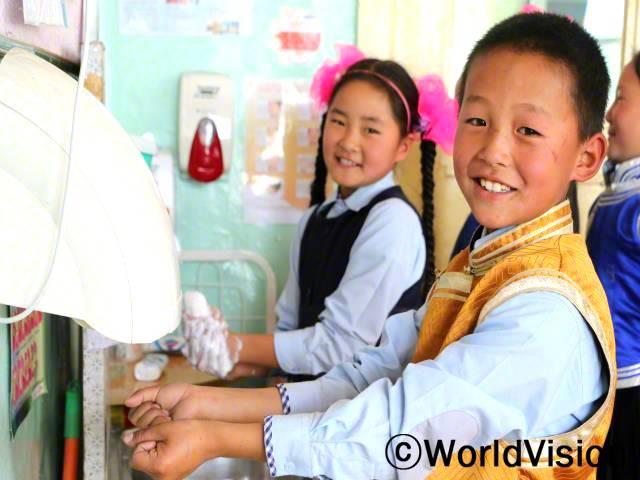세계 손씻기의 날을 맞아 같은반 친구들과 함께 깨끗한 손 캠페인에 참여했어요. 교실에 싱크대와 핸드 드라이어 그리고 비누가 생겼어요. - 트세렌돈디브, 10세, 노란색 조끼를 입은 아동년 사진