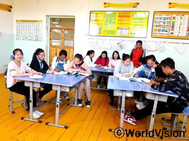 """""""월드비전에서 주최하는 다양한 교육 활동과 동아리에 항상 참여하고 있어요. 저는 월드비전에서 만든 '둘(Dul)'이라는 평화동아리 회원이기도 해요.지금은 동아리 친구들과 함께 새로운 수업을 듣고 있답니다."""" - 엔크진 (16세, 맨 왼쪽 웃고 있는 아동)년 사진"""