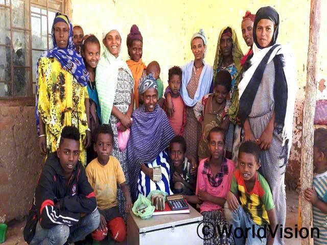 메스타왓(보라색 옷을 입은 어머니)이 지역사회의 저축그룹을 통해 재정적으로 자립하게 되었고, 자녀들을 돌볼 수 있게 되었어요.년 사진