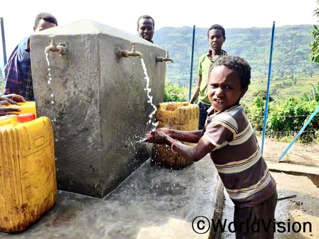 """""""월드비전의 도움으로 마을에 수도시설이 생겨서 이제 멀리까지 물을 뜨러 가지 않아도 돼요. 덕분에 공부할 수 있는 시간이 많아졌어요."""" -로바(12세)년 사진"""