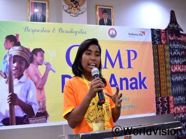 """""""어린이 대사 캠프에서 아동 보호, 옹호하는 법, 또 발표하는 법을 배웠어요. 저는 이제 마을 어른들에게 아동의 권리를 주장할 수 있답니다."""" - 엘리자베스 (15살)년 사진"""