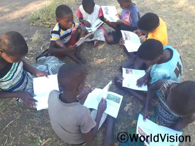 월드비전이 마을에 독서캠프를 열어준 덕분에 읽기 쓰기 실력이 늘었어요. 감사해요. 존(9세, 줄무늬 옷을 입고 있는 아동)이 말했습니다. 월드비전은 지역사회에서 독서캠프를 진행하며 아동들이 읽기 쓰기 실력을 키울 수 있도록 지속적으로 돕습니다.년 사진