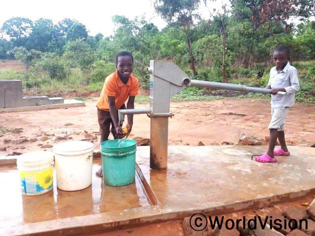 이제 아프지 않아요. 왜냐하면 깨끗하고 안전한 물을 사용하게 되었거든요. 트레포드(10세, 주황색 옷을 입은 아동)가 말했습니다. 월드비전은 마을에 수도시설을 보수하여 지역사회 아동들이 안전한 물을 사용할 수 있도록 했습니다.년 사진