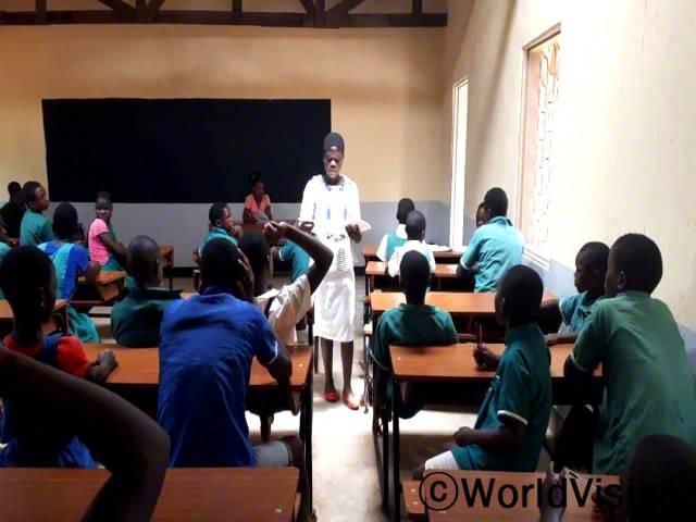"""""""후원자님 덕분에 새로운 교실과 책상이 생겨서 이제는 깨끗하고 안전한 환경에서 수업을 들을 수 있게 되었어요."""" –자넷(15세)년 사진"""