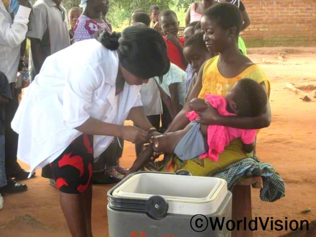 """월드비전은 정부와 협력하여 마을 사람들을 대상으로 기초보건교육을 실시하였습니다. """"저희 아이들은 예방접종을 맞은 덕분에 이제 아프지 않고 건강하게 자랄 수 있게 되었어요."""" –잭슨(세 아이의 어머니)년 사진"""
