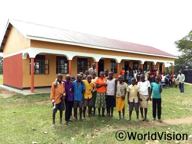 초등학교의 학생들과 선생님들이 새로 건축된 교실 앞에서 기뻐합니다. 월드비전이 이 지역의 교육적 지원으로 새 교실을 만들었습니다.년 사진
