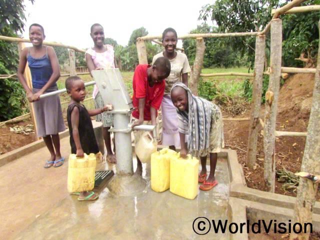 이 펌프가 생기기 전에는 물을 길으러 먼 거리를 걸어 다니곤 했어요. 그런데 지금은 이렇게 집 근처에서 수도가 있어서 깨끗하고 건강하게 지낼 수 있게 되었답니다. -아미나(8세, 오른쪽, 스카프를 두른 아동)년 사진