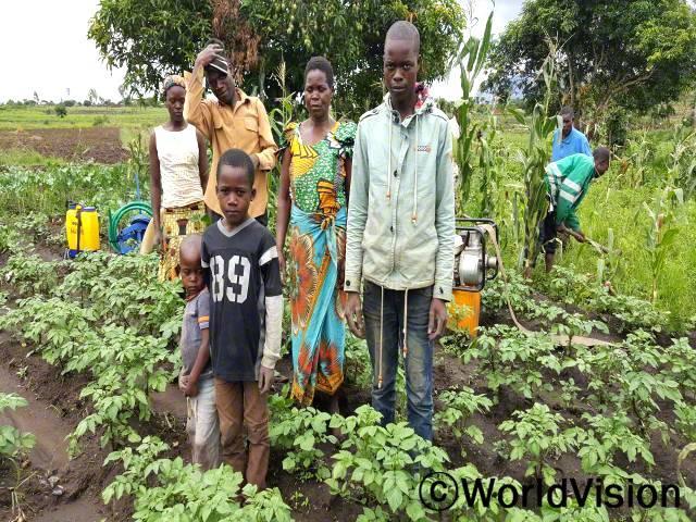 저는 다양한 농작물을 재배하는 법을 배울 수 있어서 너무 감사해요. 이제 저희 가족은 한 해 동안 충분한 움식을 먹을 수 있어요. 또한, 수확량 중 일부를 팔아서 수입을 얻고, 자녀의 학용품도 살 수 있어요. -안나(엄마, 초록색과 노란색 셔츠를 입은 사람)년 사진