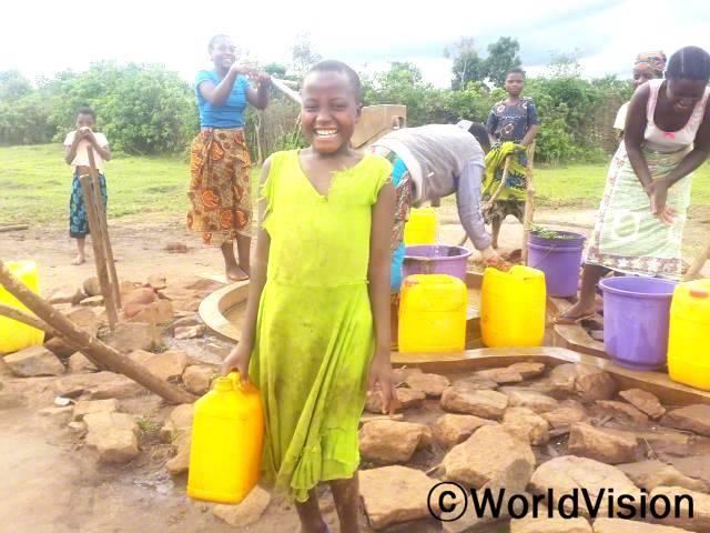저는 물을 찾아서 장거리를 걸어다녀야 했고, 학교에도 항상 늦었어요. 저희 마을에 식수시설이 생기고 나서 저는 더 이상 더러운 물을 마시지 않기 때문에 아프지 않아요. -엘루브(9세, 연두색 원피스를 입은 아동)년 사진