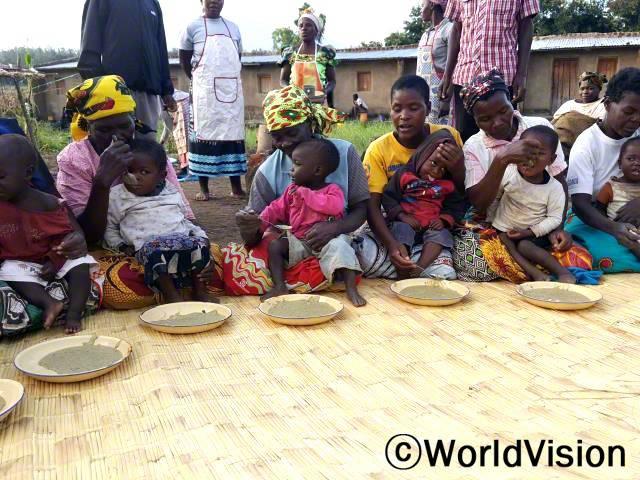 지역사회 엄마들이 모여 아이들을 건강하게 해 줄 영양이 풍부한 죽을 아이들에게 먹이고 있습니다.년 사진