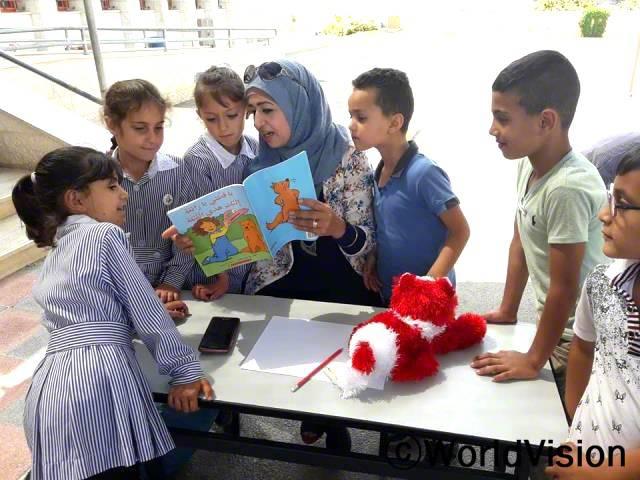 지역의 읽기 프로그램에서 엄마가 제게 책을 읽어주시는 것이 너무 좋아요. 이제 저는 이야기들을 좋아하고, 엄마는 우리가 같이 읽을 수 있는 책을 사주세요. -아흐마드(7세, 파란색 티셔츠를 입고 있는 아동)년 사진