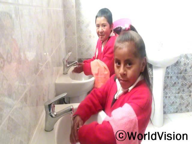 예전에 우리 학교에는 손을 씻을 수 있는 곳이 없었어요. 이제 우리는 화장실에 다녀온 뒤 매일 세면대에서 손을 씻어요. -마리아나(9세, 앞에 있는 아동)년 사진