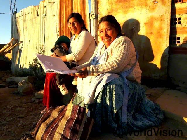 """""""마을에 사는 가정들이 건강습관을 기를 수 있도록 돕고 있어요. 조언을 드리기도 하고요. 이렇게 도울 수 있어서 정말 기뻐요."""" - 우발디나(42세, 책을 들고 있는 여성)월드비전에서 주최한 보건교육을 받은 마을 주민이 가정을 방문해 상담해주며, 보건위생관리를 지원합니다.년 사진"""