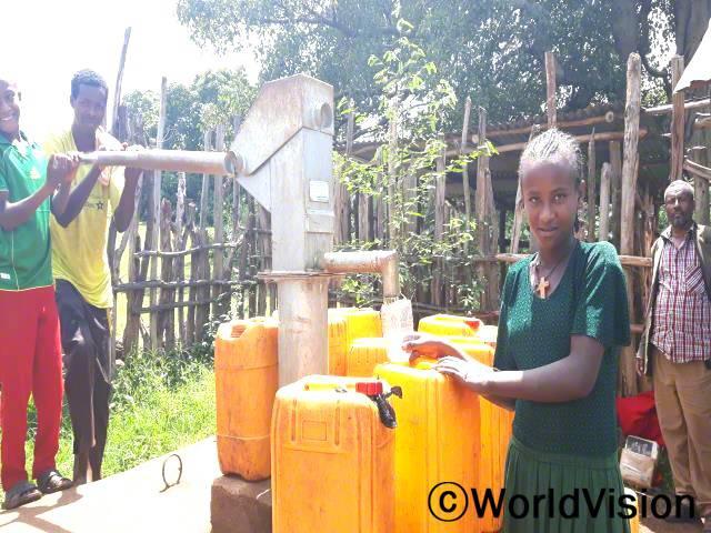 """""""물을 길러오기 위해 두 시간을 걸어가야 했어요. 근처에 수도시설이 생긴 이후 저는 숙제를 할 수 있는 시간이 생겼어요."""" -제넷(13세), 초록색 치마를 입은 아동년 사진"""