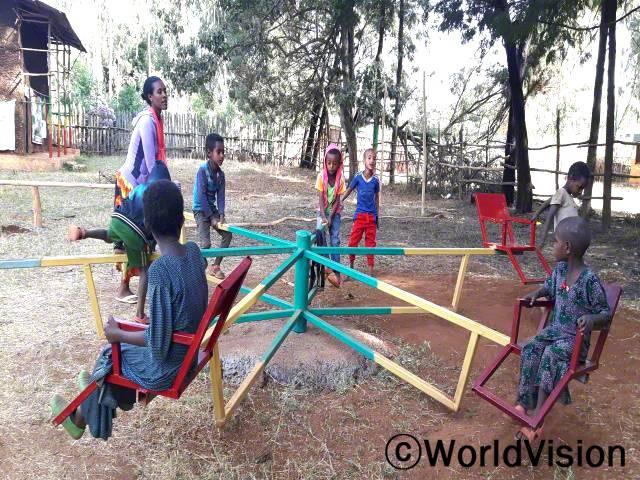 아이들이 정말 기뻐해요. 교육환경과 바깥놀이 활동 덕분에 아이들이 유치원을 좋아해요. 마을에 있는 놀이터에서 자유시간을 즐겨요. -세라마윗(교사, 왼쪽, 보라색 스웨터를 입고 있는 사람)년 사진