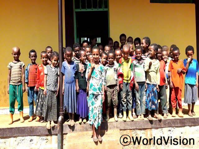 예전 교실은 더럽고 어둡고 좁았어요. 이제 교실이 확장되어서 안전하고, 넓고, 밝은 곳에서 공부하고 있어요. -티지스트(12세, 앞줄, 손을 흔들고 있는 아동)년 사진