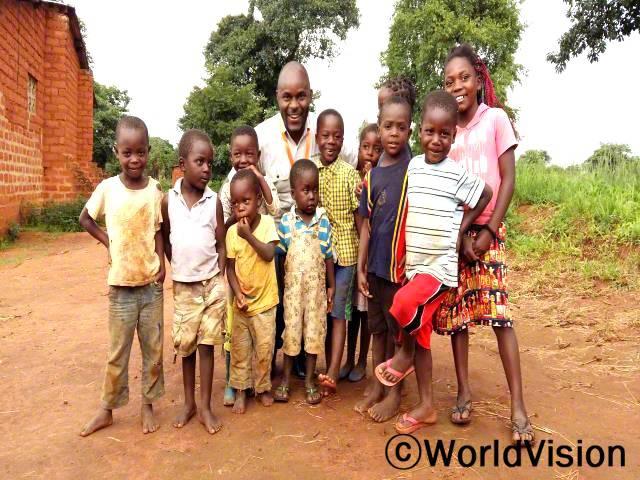 잠비아 룽가 지역개발사업장 팀장 트러스트 무틴타와 함께 있는 아동들입니다.년 사진
