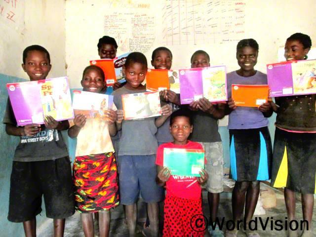월드비전이 저희 학교에 책을 지원해준 이후로, 저의 읽기능력이 늘었어요. -애니(12), 오른쪽 두번째 아동년 사진