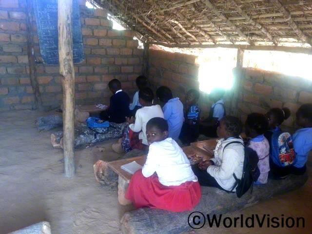 통나무에 앉아서 수업을 듣는 건 정말 힘들어요. 편안한 의자와 책상, 튼튼한 교실이 있었으면 좋겠어요. - 마조리(13세)년 사진