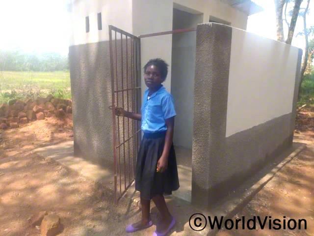"""""""전에는 더러운 화장실 때문에 병에 걸려 학교에 결석하곤 했었어요. 하지만 월드비전의 도움으로 안전하고 깨끗한 화장실이 생겨 이제는 아프지 않고 학업에 집중할 수 있게 되었어요."""" –크리스틴(13세)년 사진"""