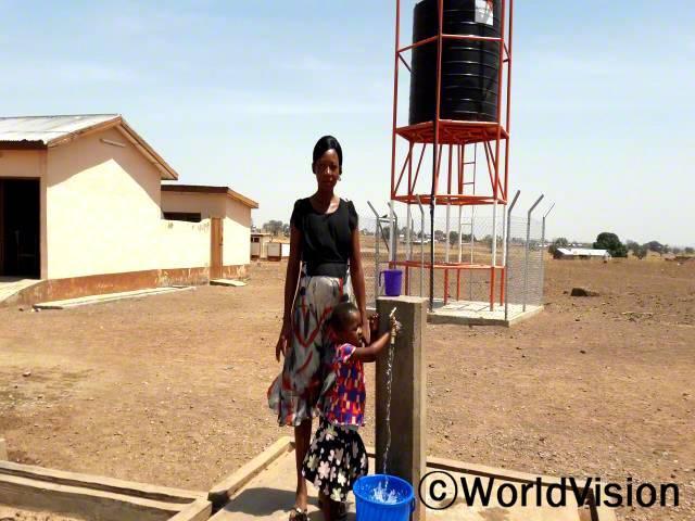 저는 아이들 중 한 명이 고열을 앓을 때마다 열을 내리기 위해 물을 찾아 45분을 걸어 다녔어요. 이제 우리 마을 보건소에 물 탱크가 있다는 것이 너무 감사해요. -아그네스(엄마, 왼쪽에 있는 사람)년 사진