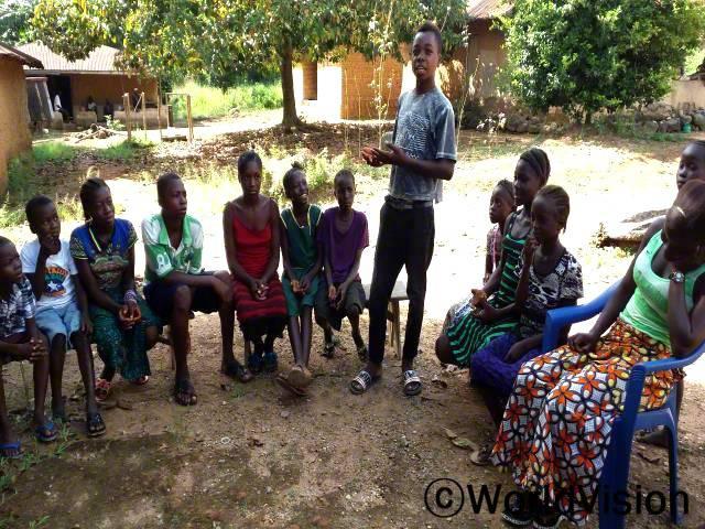 아동클럽의 중요성을 깨달았어요. 이제는 우리의 건강한 삶에 대해 부모님에게 알릴 수 있게 되었어요. -임마누엘(13세), 회색 옷을 입고 서 있는 아동년 사진
