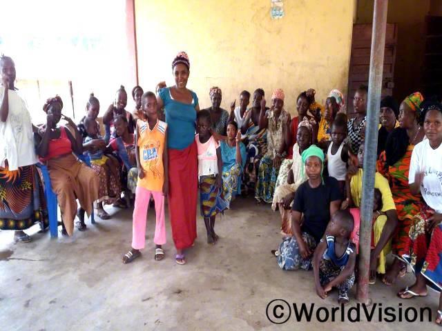 엄마들의 모임에서 배운걸 실천하면서, 지역사회도 안정되고 우리 아이들도 잘 지내게 됐어요. -카디자(파란 셔츠를 입고 서 있는 두 아이의 엄마)년 사진