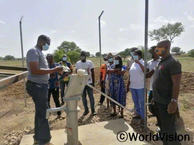 월드비전 현지 직원들이 마을 주민들에게 수도시설 사용법에 대해 알려주고 있습니다.년 사진