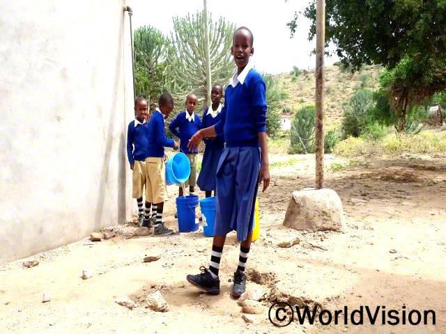 물을 길어오기 위해 먼 길을 가야해서 학교에 지각하는 날이 많았어요. 하지만 학교에 식수시설이 생겨 물을 마시고, 손을 깨끗이 씻고, 학교 화단에 물도 줄 수 있게 되었어요. -레오니아(11세, 앞쪽)년 사진