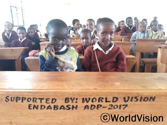 월드비전에서 교실을 만들어 주기 전에는 항상 교실이 가득 찼어요. 예전에는 4명이서 1개의 책상을 사용했었는데, 지금은 70개의 책상이 생겨서 2명이서 1개의 책상을 사용할 수 있게 되었어요. -아기네스(13세, 앞줄에 빨간 스웨터를 입고 있는 아동)년 사진