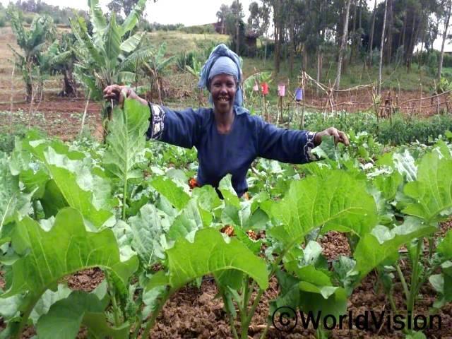 """""""토마토와 양배추 같은 채소와 바나나 농사를 한 덕에, 가족을 잘 돌보았어요. 아이들 의료비와 교육비도 감당할 수가 있었죠."""" 아델리나 와리(Adelina Waree)는 후원자님 덕분에 역량강화 교육을 받고, 밭농사를 시작하게 되었습니다.년 사진"""