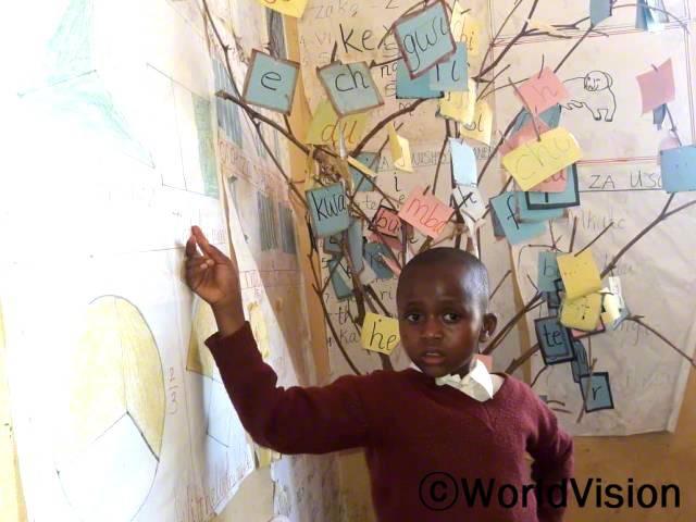 독서모임에서 한 아동이 나무에 열린 숫자들을 가리키며, 다른 친구들에게 숫자 읽는 법을 알려줍니다. 독서 모임 교사들이 연수를 받고 지역 자재로 수업 교구를 제작하는 법을 배운 덕분에 아이들의 읽기 실력이 쑥쑥 향상하고 있습니다.년 사진
