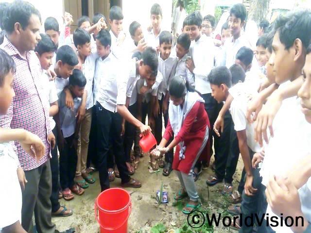 저희 학교의 학생들은 화장실에 다녀온 뒤나 밥이나 간식을 먹기 전에 손을 씻어야 한다는 것을 배웠어요. -라이한(12세, 물을 붓고 있는 아동)년 사진