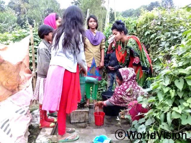 """""""후원자님 덕분에 마을에 수도시설이 생겨 이제는 안전하고 깨끗한 물을 마음껏 마실 수 있게 되었어요. 정말 감사해요!"""" -엘리자베스(13세, 정면을 바라보고 서있는 소녀)년 사진"""