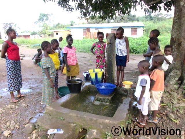 """""""집 근처에 식수시설이 생겨 물을 받는데 시간이 오래 걸리지 않아요. 덕분에 학교에 늦지 않게 가고 있죠."""" 행복한 표정으로 말하는 핀다입니다.깨끗한 물을 확보하는 것은 레이 지역 내 많은 마을에서 정말 중요한 일입니다. 사진은 사업장 등록아동들이 학교에서 마실 물과 손 씻을 물을 받고 있는 모습입니다.년 사진"""