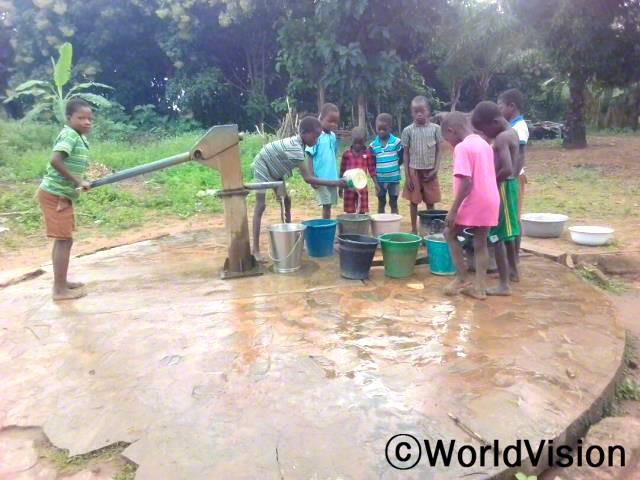 벤자민(10세)이 친구들과 함께 마을에 새로 생긴 수도시설에서 물을 끌어올리고 있어요.년 사진
